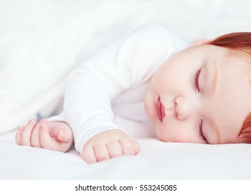 beautiful redhead infant baby sleeping peacefully in bed
