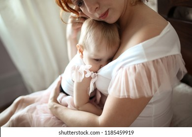beautiful redhead mother breastfeeding toddler daughter on a bed in a real casual room, the concept of tenderness and breastfeeding