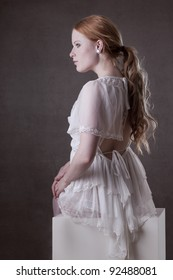Beautiful redhead posing in a white dress