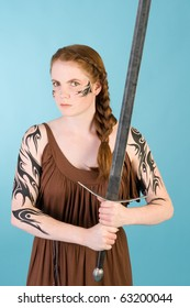 Beautiful redhead warrior girl in celtic tribal makeup