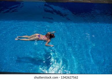 Beautiful redhead woman in bikini swims in the pool. View from above