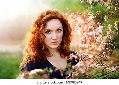 beautiful redhead woman in a blossoming garden