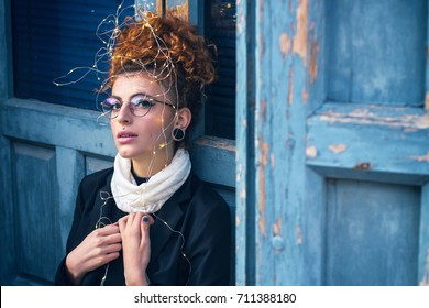 Beautiful redhead woman with christmas lights wearing urban style