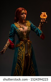 Beautiful redhead woman in cosplay costume with magic lamp on grey background
