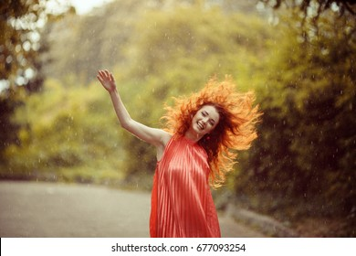 Beautiful redhead woman dancing in the rain in blooming spring garden. Happiness concept