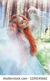 Beautiful redhead woman forest nymph in a blue transparent light dress in the woods spinning in dance. Red hair girls. Art fashion portrait of fairy woman fairy tale in summer forest