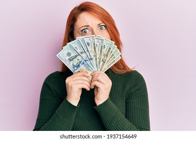 Beautiful redhead woman holding dollars close to face in shock face, looking skeptical and sarcastic, surprised with open mouth