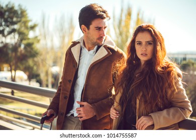 Beautiful redhead woman looking sensually at camera standing with elegant man in airport.