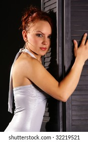 Beautiful redhead woman posing on black door
