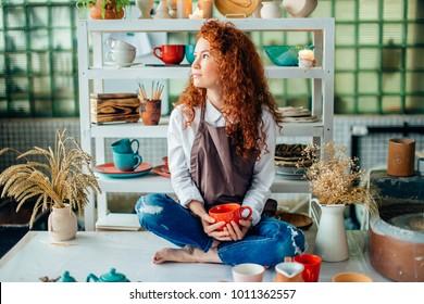 Beautiful redhead woman sitting in lotus pose in clay shop