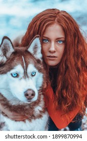 Beautiful redhead woman in snow with red husky