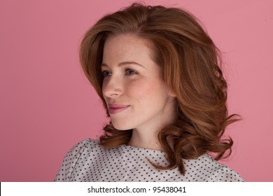 Beautiful redhead woman standing at an angle to the camera gazing off into the distance