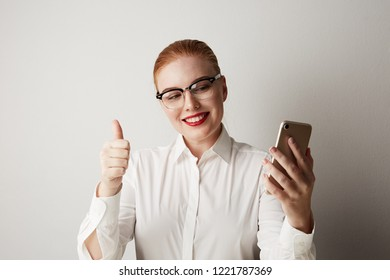 Beautiful redhead woman using mobile phone at office over gray background