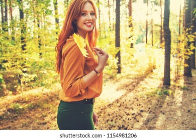 beautiful redhead woman for a walk in autumn forest