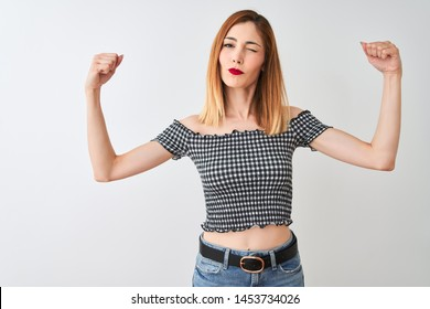 Beautiful redhead woman wearing casual t-shirt standing over isolated white background showing arms muscles smiling proud. Fitness concept.