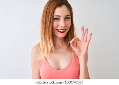 Beautiful redhead woman wearing casual pink t-shirt standing over isolated white background doing ok sign with fingers, excellent symbol