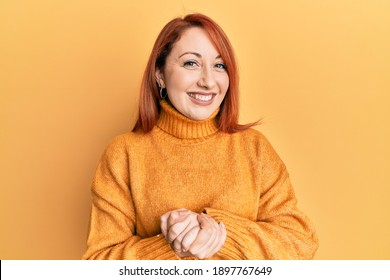 Beautiful redhead woman wearing casual winter sweater over yellow background with hands together and crossed fingers smiling relaxed and cheerful. success and optimistic