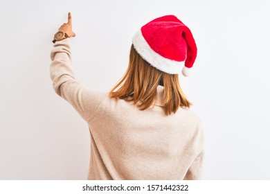 Beautiful redhead woman wearing christmas hat over isolated background Posing backwards pointing ahead with finger hand