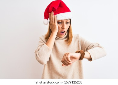 Beautiful redhead woman wearing christmas hat over isolated background Looking at the watch time worried, afraid of getting late
