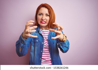 Beautiful redhead woman wearing denim shirt and striped t-shirt over isolated pink background Shouting frustrated with rage, hands trying to strangle, yelling mad