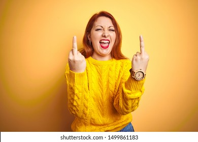 Beautiful redhead woman wearing winter sweater standing over isolated yellow background Showing middle finger doing fuck you bad expression, provocation and rude attitude. Screaming excited