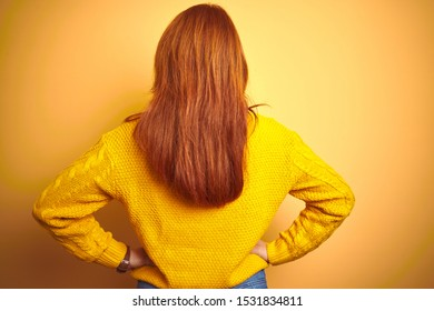 Beautiful redhead woman wearing winter sweater standing over isolated yellow background standing backwards looking away with arms on body