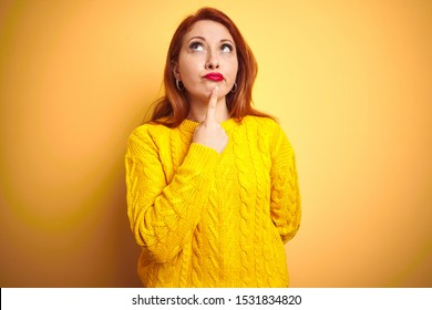 Beautiful redhead woman wearing winter sweater standing over isolated yellow background Thinking concentrated about doubt with finger on chin and looking up wondering