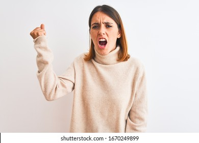 Beautiful redhead woman wearing winter turtleneck sweater over isolated background angry and mad raising fist frustrated and furious while shouting with anger. Rage and aggressive concept.