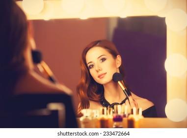 Beautiful redhead women applying makeup near mirror