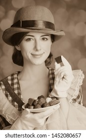 Beautiful redhead women with candy. Photo in retro style with bokeh at background.