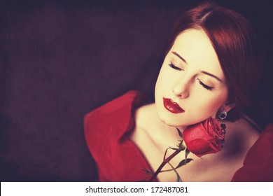 Beautiful redhead women with rose. Photo in old color image style.