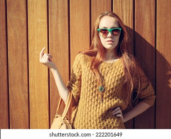 Beautiful redheaded girl with fashionable big bag in sunglasses standing near wooden wall
