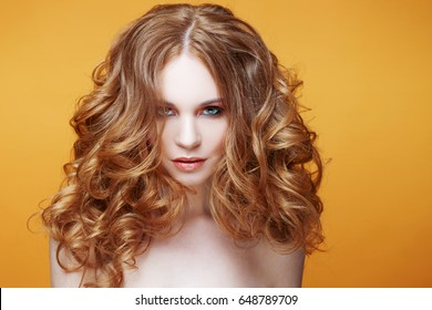 Beautiful redheaded girl with luxurious curly hair. Studio portrait on yellow background. Luxuriant hair