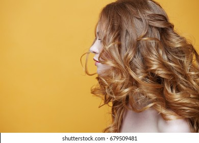 Beautiful redheaded girl with luxurious curly hair. Portrait in profile. Free space left. Studio portrait on yellow background.