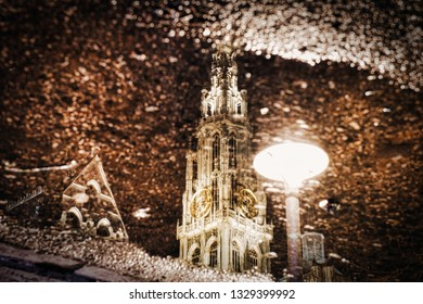 A beautiful reflection of Antwerp Cathedral in a small pond of water on a rainy day.