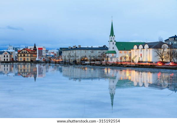 Beautiful reflection of the cityscape of Reykjavik and the Free church in lake Tjornin at the blue hour in winter