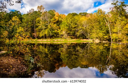 Beautiful reflections of the colorful trees and the cloudy skies are captured by the clear waters of Eno River in Durham, North Carolina. This park is just few miles away from Duke University.