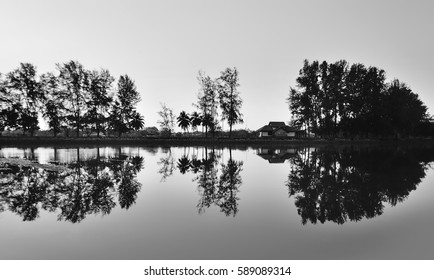 Beautiful reflections of house  at Lake  in the early morning mist, in black and white. ( soft and grain effect)