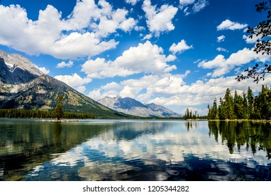 Beautiful reflections of the sky and clouds upon Leigh Lake, dominate the scene in Grand Teton National Park in Wyoming.