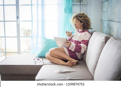 beautiful relaxed lady at home witting on the sofa and drinking a healhty water and lemon beverage while work with a tablet connected to internet manage on line office and shop. alternative lifestyle