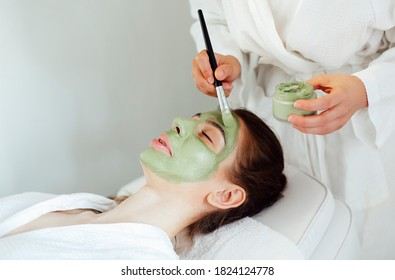 Beautiful relaxed woman having green clay face mask in spa salon