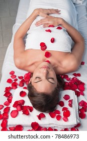 Beautiful relaxed woman lying on a massage table with rose petals around