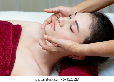 Beautiful relaxed woman receiving facial massage with aroma oil