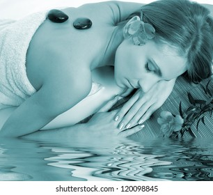 Beautiful relaxing woman with stones on her back in a Spa. Blue option