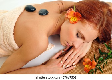 Beautiful relaxing woman with stones on her back in a Spa