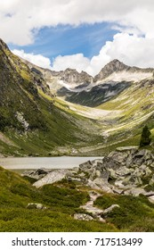 The beautiful remote Lake Dorfersee in Austria's Hohe Tauern nature reserve with the Kalser Tauern mountain range in the background on a windy summer day.