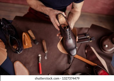 beautiful repaired shoes in man's hands. close up top view photo