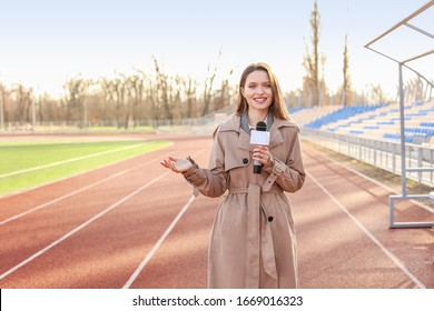 Beautiful reporter with microphone at the stadium