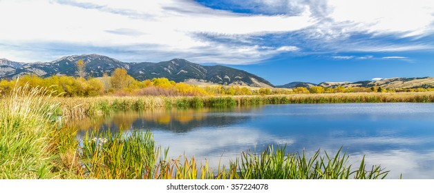 A beautiful reservoir in autumn fields at the foot of the Bridger mountain range in Cherry Creek Nature Preserve on the outskirts of Bozeman, Montana