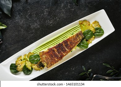 Beautiful Restaurant Plate of Baked Halibut Fillet and Broccoli in Different Textures Top View. Exquisite Italian Dish of Grilled Flatfish or Sole Fish on Natural Black Stone, Leaves Background